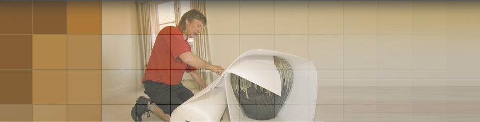 Man bubble wrapping up a large vase